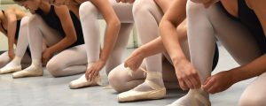 Dancers tying their shoes before class